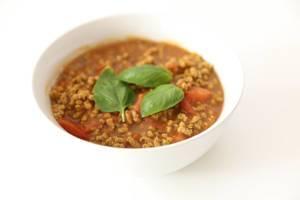 Vegane Bolognese aus Sonnenblumenkernen, zubereitet in Tomatensauce und in einer weißen Schüssel mit Basilikumblättern serviert