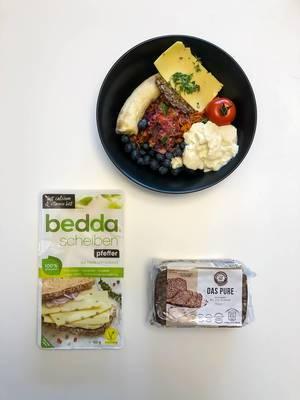Vegane Ernährung mit Hafervollkornbrot ohne Mehl und Hefe, Bedda Scheiben auf pflanzlicher Basis, Beeren, Tomate und Banane. Aufnahme von oben