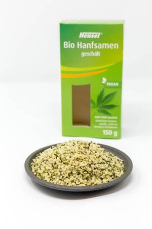 Vegane geschälte Bio-Hanfsamen auf einem Teller vor der Verpackung auf weißem Hintergrund