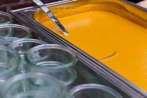 Vegane Kürbis-Kokos-Suppe in einem Warmhaltebehälter bei einem Buffet