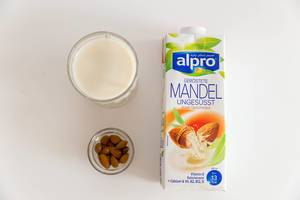 """Vegane Milchverpackung von Alpro """"Geröstete Mandel ungesüsst"""" liegt flach auf dem Tisch, neben einer Nussschale und einem laktosefreien Milchglas"""