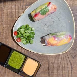Vegane Rainbow Sommerrollen mit Avocado, Mango, Paprika, Rotkohl, Koriander, Karotten, Eisbergsalat, und Reisnudeln serviert mit drei verschiedenen Saucen