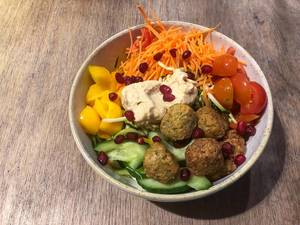 Vegane Schüssel mit Falafel, Hummus, Karotten, Kirschtomaten, Mango, Gurken, Granatapfelkernen: Aufnahme von oben vor hölzernem Hintergrund