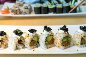 """Vegane Sushiplatte """"Lucky No Fish"""" in einer Reihe, mit Kimchi-Sesamkernen verziert und veganem Kaviar-Belag, mit Essstäbchen im Hintergrund"""