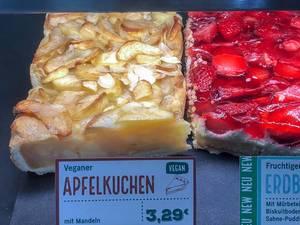 Veganer Apfelkuchen mit Mandeln und Preisschild, neben einem Stück Erdbeerkuchen in der Auslage