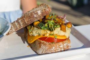 Veganer Burger im Motto am Fluss mit Karotten-Humus, eingelegten roten Zwiebeln, grünem Spargel, Edamame & Mango-Papaya Salat