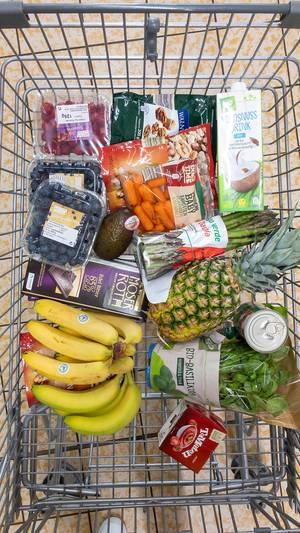Veganer Einkauf im Einkaufswagen mit Beeren, Schokolade, Bananen, Ananas, frischem Basilikum, Baby-Karotten, Spargel, Kokosmilch, und Nüssen