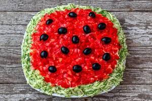 Veganer Salat mit Tomaten, Gurken und Oliven auf einem weißen Teller auf einem Holztisch