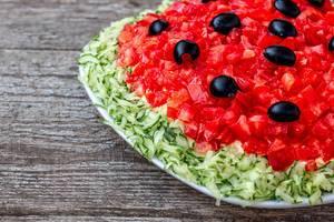 Veganer Salat mit Tomaten, Gurken und Oliven in Nahaufnahme