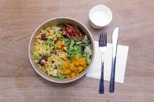 Veganes, asiatisches Mittagessen: Hirsebowle mit Erbsen, Reis, Kidneybohnen, Blumenkohl und Tofu, auf einem Holztisch
