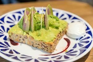 Veganes Avocado Toast aus Vollkorn-Brot mit Guacamole, pochiertem Ei und Acai Soße im Flax&Kale Restaurant in Katalonien
