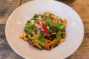 Veganes Bio-Tofu in dünnen Scheiben gebraten mit Zwiebeln, Pak-Choi, Champignons, Zuckererbsen, Bandnudeln und Erdnüssen mit Limetten-Chili Sauce