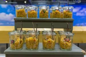 Veganes Couscous Salat mit Tomaten, Mais, roten Zwiebeln und Keimen in kleinen Gläschen auf dem BarCamp in Bonn