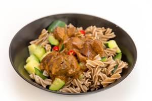 Veganes Gericht im Nahaufnahme: Pasta mit Jackfruit, Gurkeln und rotes Paprika im Currysauce auf schwarzem Teller