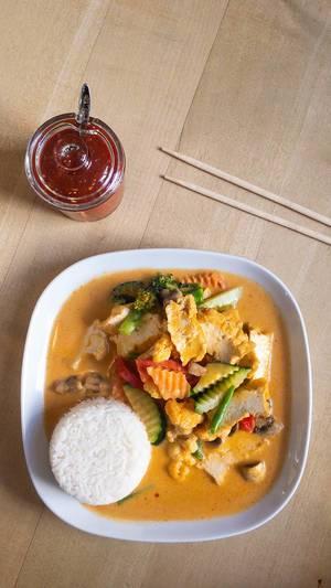 Veganes rotes Thai Curry mit Gemüse, scharfer Soße und Essstäbchen