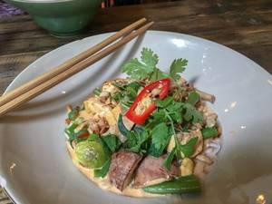 Veganes Tofu-Pilz Gericht im Sauce mit grünes Topping und Paprika mit Eßstäbchen am Rande des Tellers