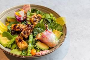 Veganisches Tofu-Gericht mit Spinat, Spargel, Avocado, Minze und Sommerrollen in brauner Schale im Nahaufnahme