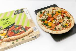 Veganz Pizza Verdura - deep frozen pizza with mushrooms, spinach, paprika and tomatoes and packaging  on a black plate and white background