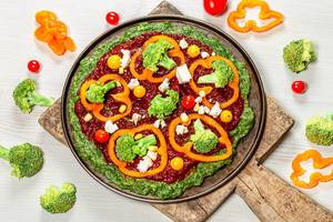 Vegetable pizza with tomatoes, pepper, broccoli and feta cheese with ingredients on the table (Flip 2019)