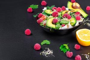Vegetable salad with avocado, greens, onion micro-greens and raspberries on a black background