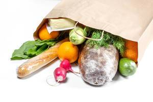 Vegetables, fruits, greens, bread and cheese in a paper bag on a white background. Food shopping concept