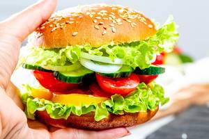 Vegetarian Burger with lettuce, cucumber, tomatoes, onions, bell pepper and sauce in a woman