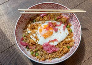 Vegetarian meal in white-red plate with chopsticks: fried rice with onions, carrots, peas, ginger and fried egg