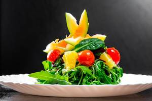 Vegetarian salad with herbs and avocado on white plate