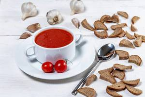 Vegetarian tomato soup with crackers, cherry tomatoes and garlic on white wooden background (Flip 2019)