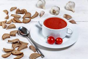 Vegetarian tomato soup with crackers, cherry tomatoes and garlic on white wooden background