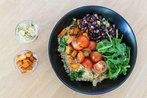 Vegetarische Bowl mit Süßkartoffeln, Cherry-Tomaten, Rukola und roten Bohnen. Draufsicht