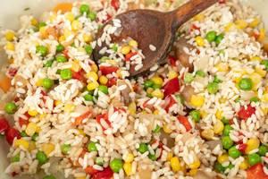 Vegetarische Ernährung: Risotto mit Erbsen, Mais, Tomaten und Paprika in Nahaufnahme