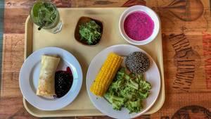 Vegetarische Mahlzeit in Russland: Crêpe mit Preiselbeersauce, gekochter Brokkoli und Mais, Swekolnik und Chuka Algensalat