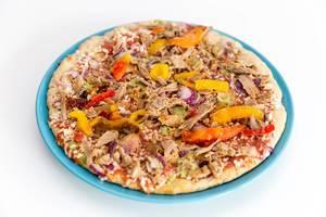 Vegetarische Protein Pizza mit Leinsamen, Quinoa und pulled Soybeans von Garden Gourmet ausgepackt gefroren auf einem Teller