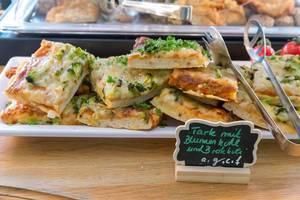 Vegetarische Tarte mit Blumenkohl und Brokkoli auf einer weißen Platte am Essensbüfett