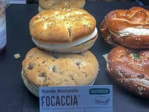 Vegetarische Tomaten-Mozarella Focaccia in der Auslage mit anderen Backwaren