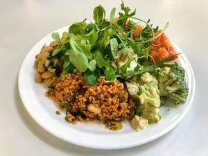 Vegetarischer gesunder Teller mit frischen Salaten, verschiedenem Gemüse und Couscous