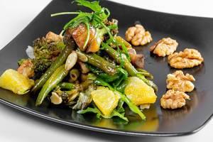 Vegetarischer Saat mit Spargel, Brokkoli, grünen Salatblättern, Orange und Walnüssen