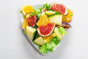 Vegetarischer Salat mit Feigen, Mango, Orange und grünen Salatblättern, auf einem dreieckigen Teller