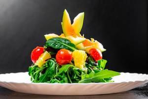 Vegetarischer Salat mit Kräutern, Tomaten und Avocado vor dunklem Hintergrund