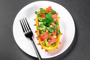 Vegetarisches Dessert: eine halbe Kiwanofrucht gefüllt mit Avocado- und Grapefruitstückchen aus oben fotografiert