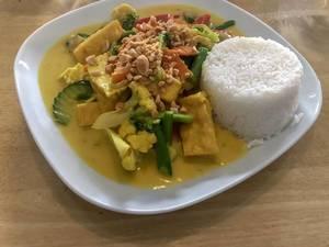 Vegetarisches Mittagessen mit Kurkuma Curry, Gemüse wie Blumenkohl, Paprika, Karotten und weißem Reisturm