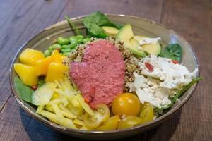 """Vegetarisches Mittagessen """"Spring Time Bowl"""" mit Quinoa, Joghurt-Minz-Dressing, Avocado, gelber Bete, Mango, Edamame, Goji, Papadam, Rote-Bete Mayo"""