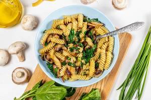 Vegetarisches Mittagessen: Sicht von oben auf eine Schüssel mit Nudeln, Kräutern und Pilzen