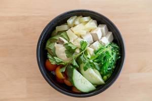 Veggie Bowl Salat mit Gurken, Tomaten, Ananas Tofu und Petersilie in der Aufsicht