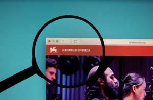 Venice Biennale website on a computer screen with a magnifying glass
