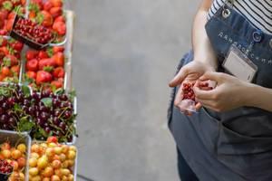 Verkäuferin mit Wald-Erdbeeren in der Hand