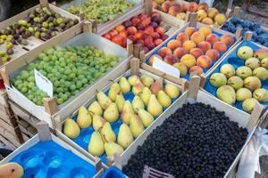 Verkaufsstand auf einem Marktplatz mit frischen Früchten in Körben