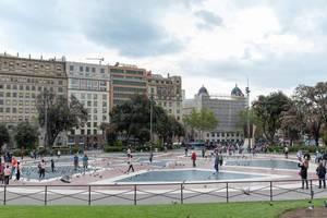 Verkehrsknotenpunkt Placa de Catalunya mit Tauben und Menschen auf sternförmigem Muster der rot-blauen Bodenfliesen in Barcelona, Spanien