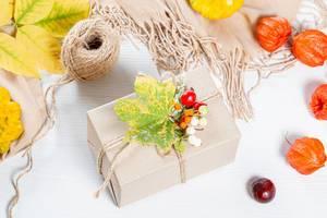 Verpacktes Geschenk mit gelben Blättern und Beeren umrandet von Schal und Fäden auf weißem Holztisch zu Thanksgiving